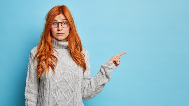 Surprised redhead woman sees incredible thing points away on copy space dressed in knitted sweater.