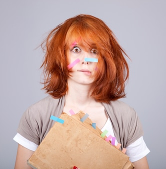 Surprised redhead woman with book and notes on face.