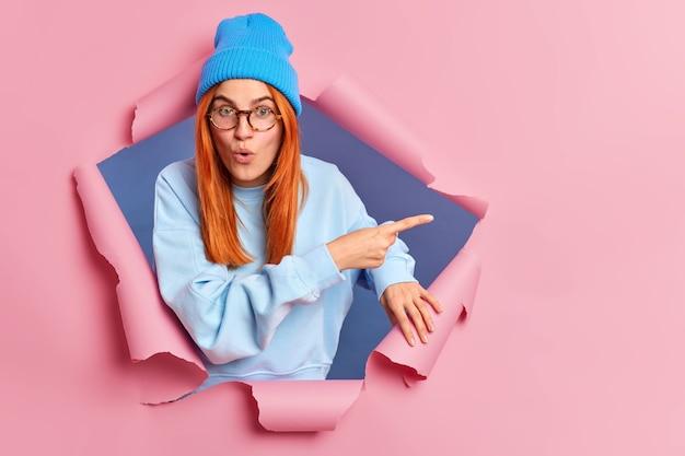 La giovane donna europea dai capelli rossi sorpresa ha uno sguardo stupito che punta di lato attraverso il foro della carta