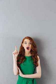 Surprised redhead young lady in green dress have an idea.
