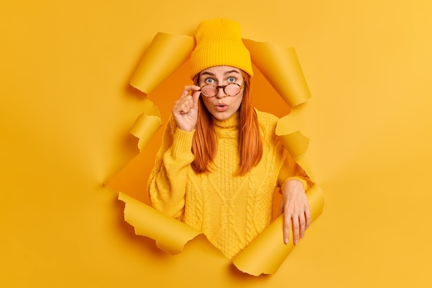 Surprised redhead young woman stares shocked through glasses impressed by something wears hat and sweater breaks through yellow paper ripped hole.