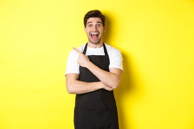 黄色の背景に立って、店のプロモーションのオファーを示して、指の左上隅を指している黒いエプロンで驚いたセールスマン。