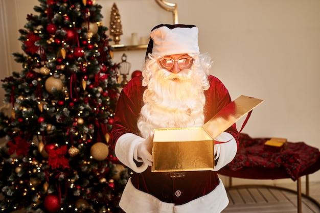 아름 다운 크리스마스 트리 근처 마법의 빛나는 선물 놀된 산타 클로스. 새 해와 메리 크리스마스, 해피 홀리데이 개념