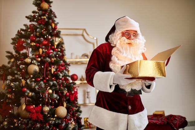 Удивленный санта-клаус с волшебным светящимся подарком возле красивой елки.