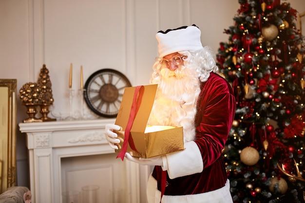 아름 다운 크리스마스 트리 근처 마법의 빛나는 선물 놀된 산타 클로스.