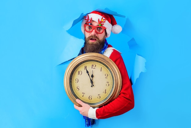 Surprised santa man with vintage clock through paper hole new year countdown time to celebrate