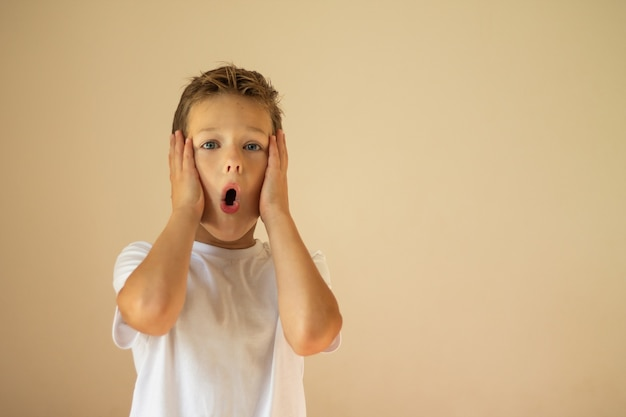 A surprised or scared boy of 7-10 years old in a white t-shirt stands and shouts with his hands on his cheeks.