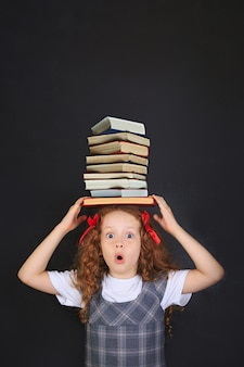 Surprised school girl with stacks of books on her head.