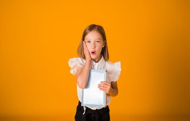 흰 블라우스를 입은 놀란 여학생은 노란색 배경에 파란색 공책을 들고 공간 사본을 들고 있다