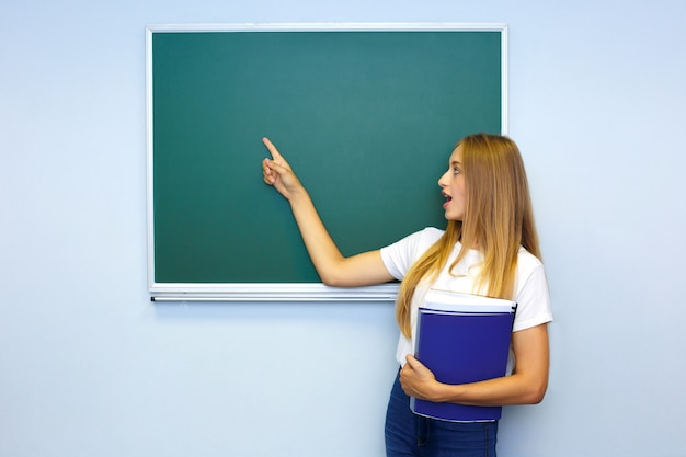 Surprised schoolgirl near the blackboard with a folder in her hand shows a finger on the board.