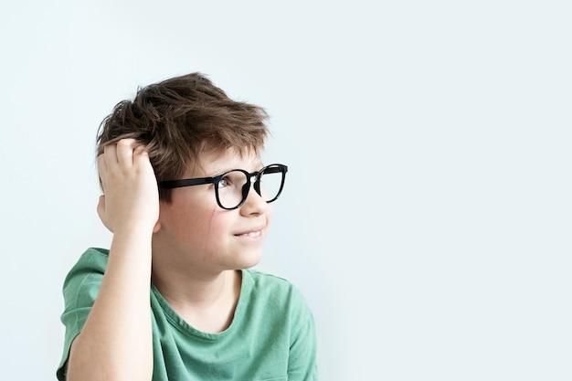 녹색 티셔츠와 안경에 놀란 스크래치 소년 잠겨있는 그의 머리를 긁적