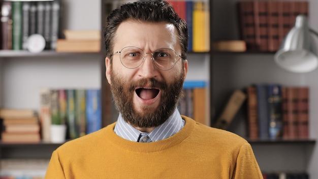 놀란 비명을 지르는 남자. 분개한 수염 난 남자 교사나 안경을 쓴 사업가가 카메라를 보고 비명을 지른다. 미디엄 샷