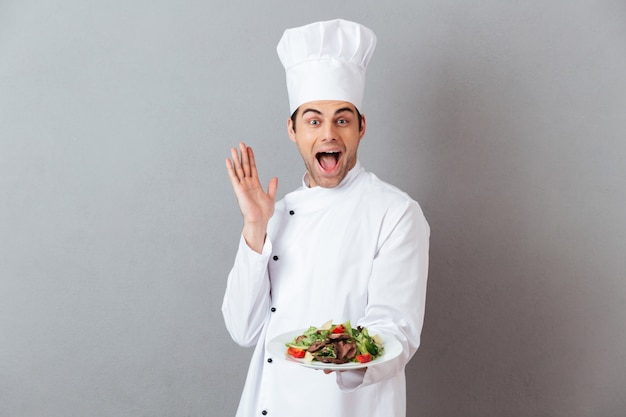 Surprised screaming young cook holding salad.