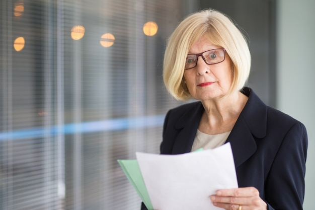 Surprised senior business lady holding documents