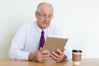 Surprised senior business man reading news on tablet computer at office desk