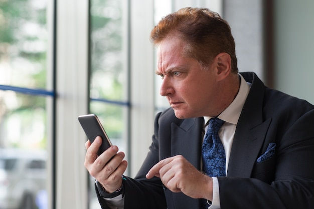 Surprised senior businessman reading message