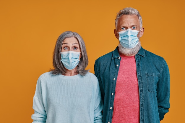 Surprised senior couple in protective facemasks looking at camera