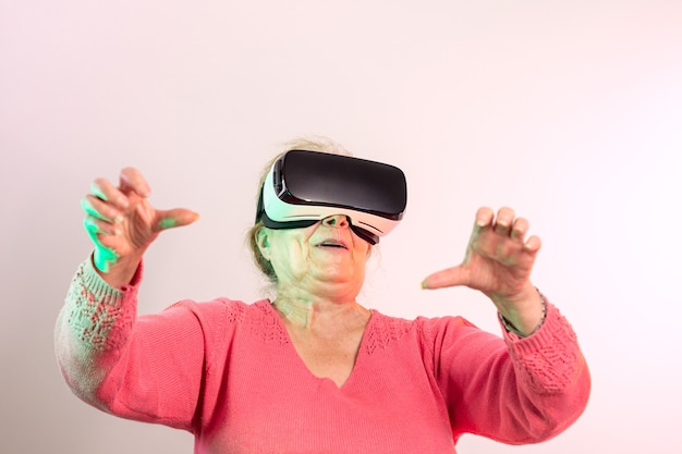 Surprised senior woman enjoying wearing pink sweater wearing virtual reality glasses and raised hands looking straight ahead illuminated with red and green lights on light background