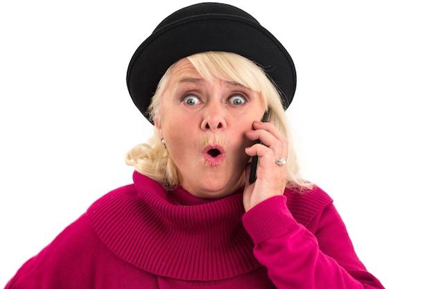 Удивленная старшая женщина, держащая мобильный телефон.