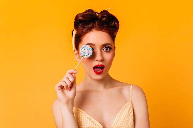 ロリポップを持って驚いた官能的な女性。甘いお菓子と魅力的なピンナップガールのスタジオショット。