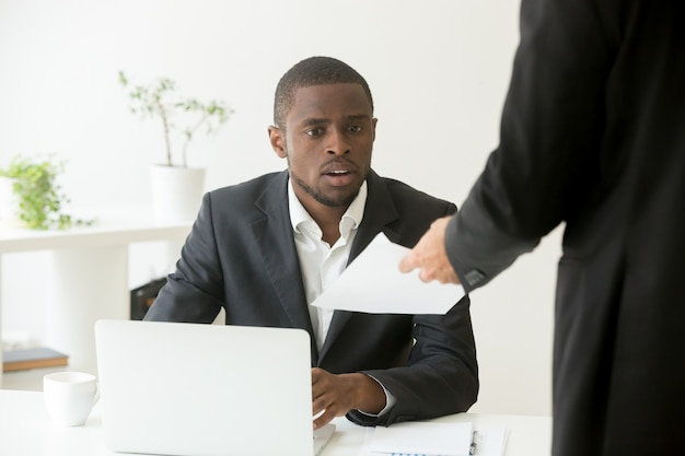 Surprised shocked african businessman getting unexpected notice from caucasian colleague