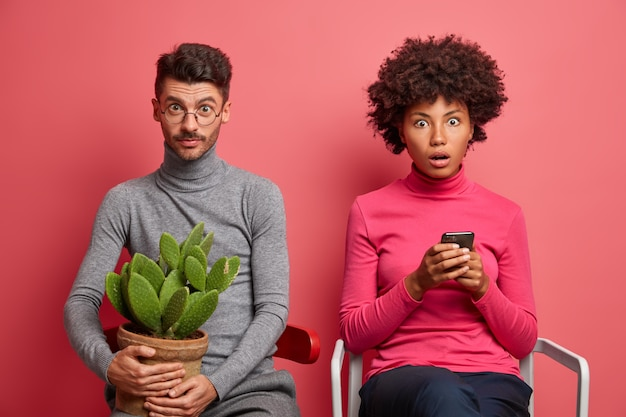 Surprised shocked afro american woman uses mobile phone and reads news online stares bugged eyes wondered man poses near on chair with cactus pot on hands. interracial couple indoor over pink wall