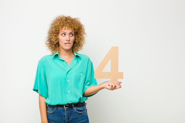Surprised, shocked, amazed, holding a number 4.