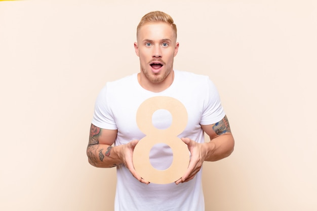 Surprised, shocked, amazed, holding a number 8.