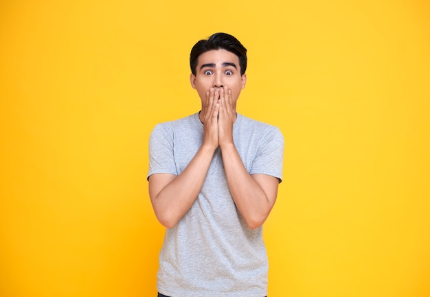 Surprised and shocked asian man covering mouth with hands isolated on bright yellow background.