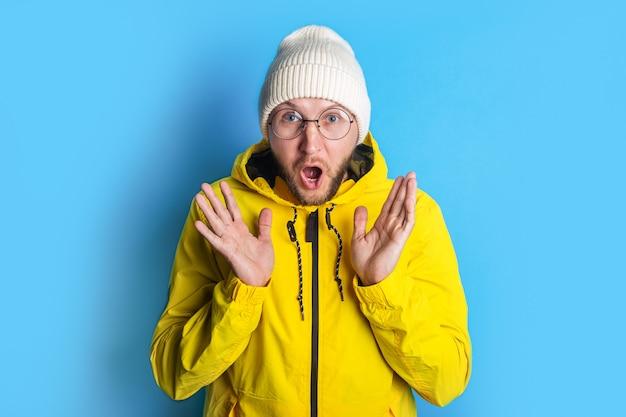 青い背景の黄色いジャケットに眼鏡をかけて驚いたショックを受けたひげを生やした若い男。
