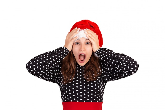 Surprised shocked beautiful woman in dress looking at the camera. emotional girl in santa claus christmas hat isolated