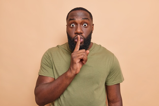 Surprised shocked black bearded man keeps index finger over lips makes silence gesture stunned by gossips or rumors shows shushing gesture wears casual t shirt isolated over beige wall