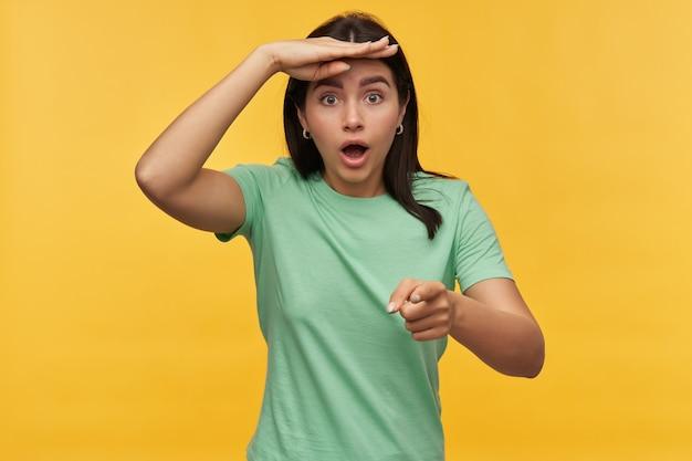ミントのtシャツを着た驚いたショックを受けたブルネットの若い女性は、額に手を当て、遠くを見て、黄色の壁越しにあなたを指さしている