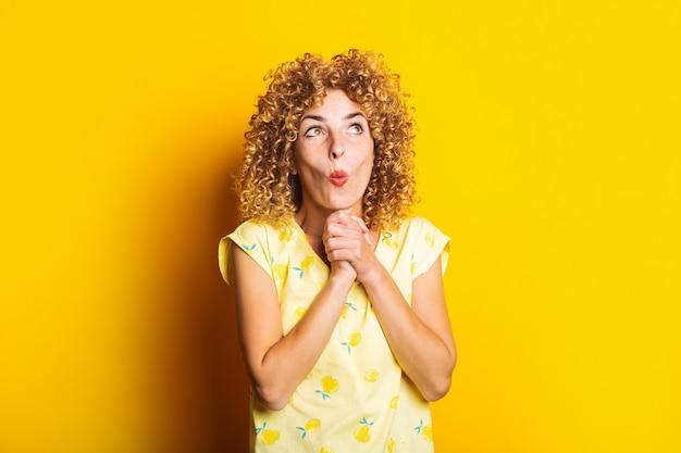 黄色の背景のあごの下で握りしめられた手で驚いたショックを受けた縮れ毛の若い女性