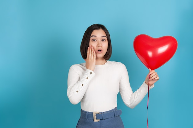 Surprised, shocked young asian woman with open mouth holds a flying heart-shaped balloon