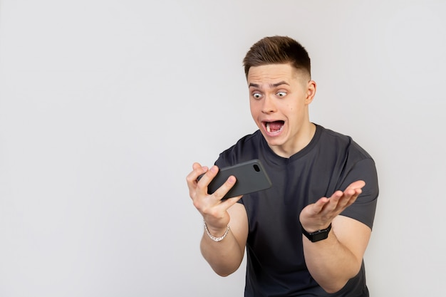 A surprised, shocked young man holds a smartphone in his hands and looks at the display with his mouth open and big eyes