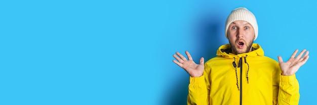 青い背景の黄色いジャケットで驚いたショックを受けた若い男。バナー。