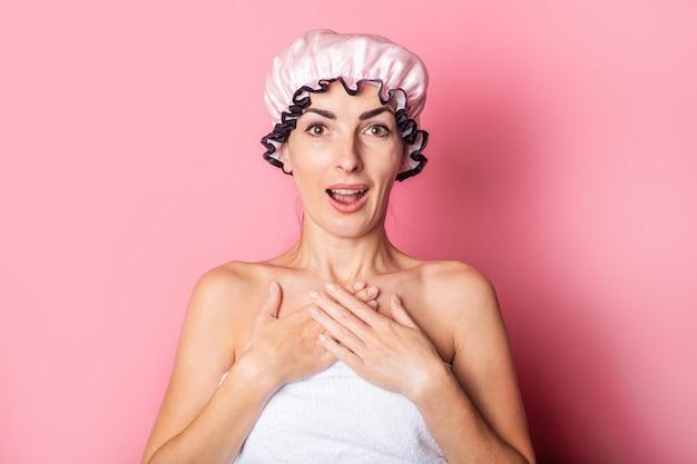 Удивленная шокированная молодая женщина в розовой шапочке для душа на розовом фоне.