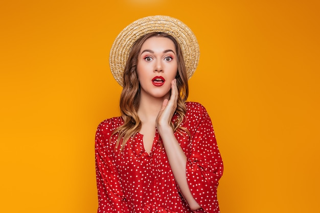 Surprised shocked young woman in a straw hat in a red summer dress red lipstick looks directly at the camera. portrait of a shocked girl in summer clothes on an orange wall sale concept