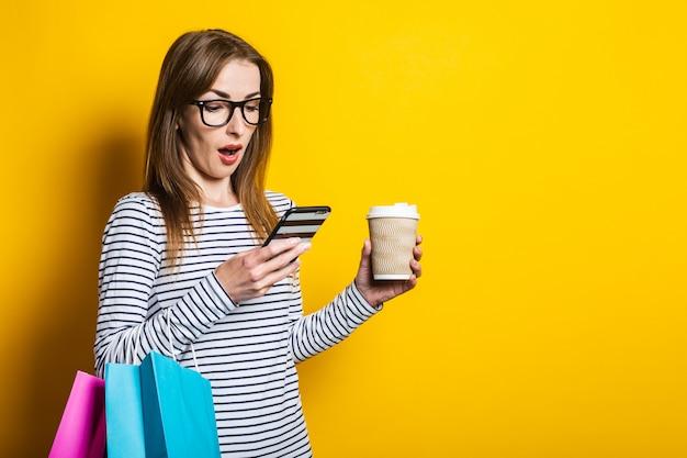黄色の背景に紙コップで、ショッピングバッグの電話で驚いてショックを受けた若い女性