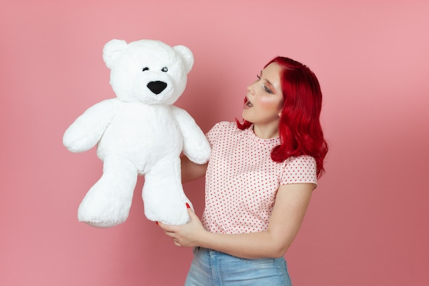 Surprised, shocked young woman with an open mouth and red hair holds a large white teddy bear