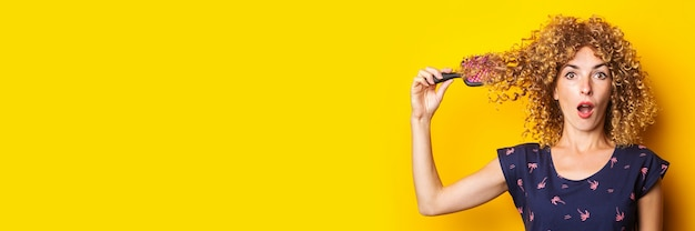 Surprised shocked young woman with tangled comb in curly hair on yellow background. banner.