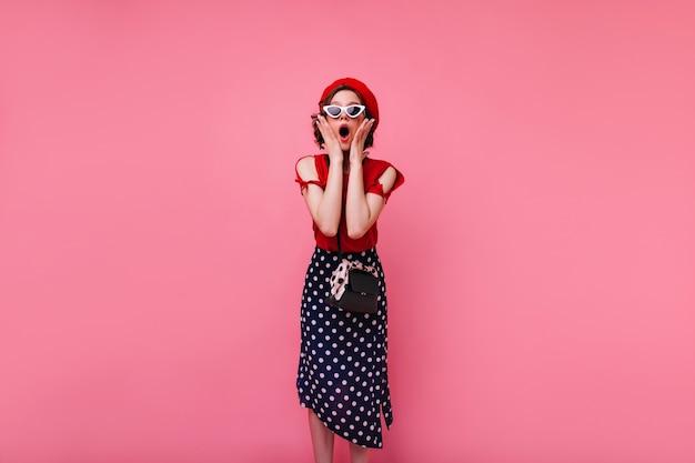 Ragazza francese dai capelli corti sorpresa in posa. foto dell'interno della donna alla moda in gonna lunga che esprime stupore.