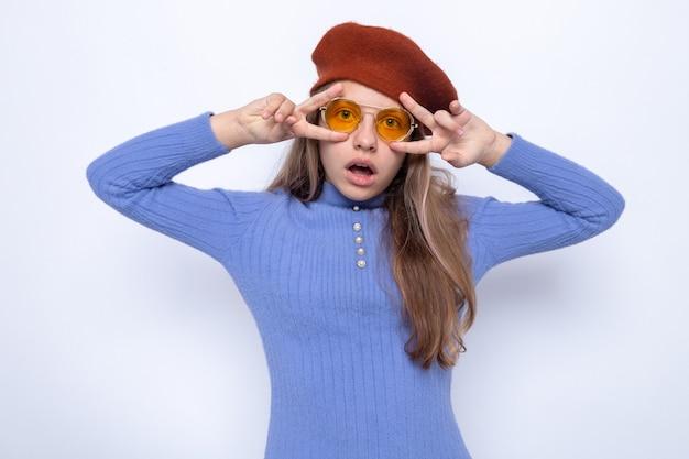 帽子と眼鏡をかけている美しい少女が平和のジェスチャーを示して驚いた