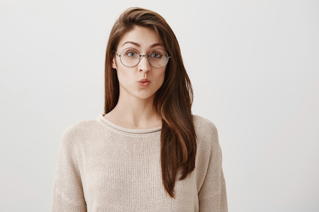 Surprised silly girl pouting, wearing trendy prescribed glasses