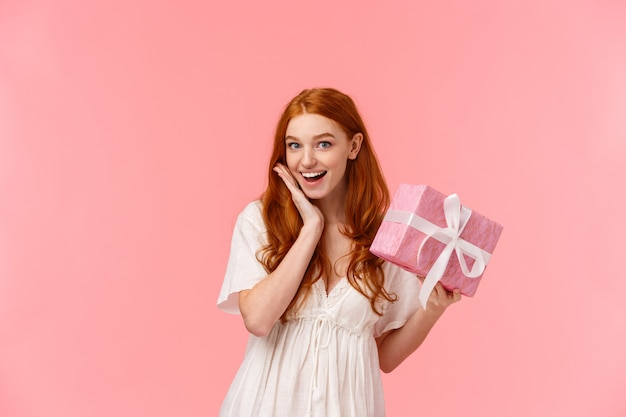 Surprised, silly and lovely feminine redhead girl receive gift, look amused and wondered, didnt expect, smiling pleased, holding wrapped present, wonder whats inside, standing pink wall