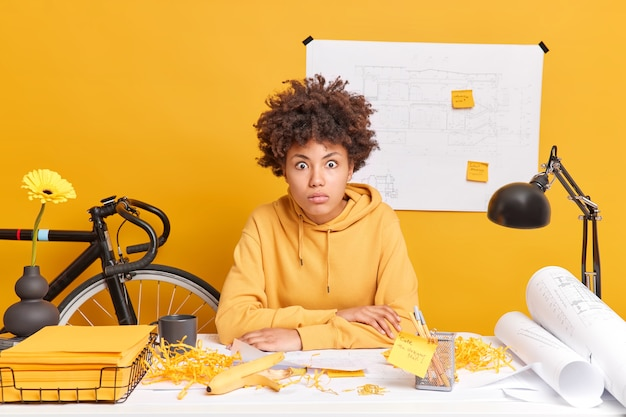 Surprised skilled female engineer works on building blueprint stares shocked, realises deadline involved in working process dressed in sweatshirt
