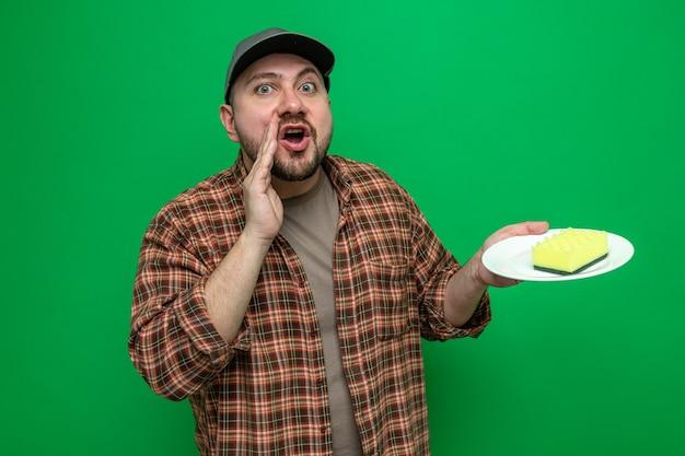 Uomo delle pulizie slavo sorpreso che tiene la mano vicino alla bocca e tiene la spugna sul piatto