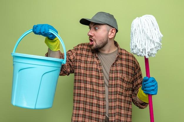 Uomo delle pulizie slavo sorpreso con guanti di gomma che tengono secchio e mop