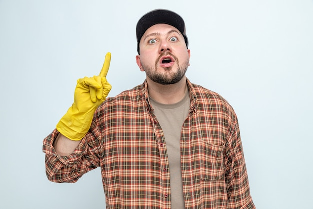 Surprised slavic cleaner man with rubber gloves pointing up